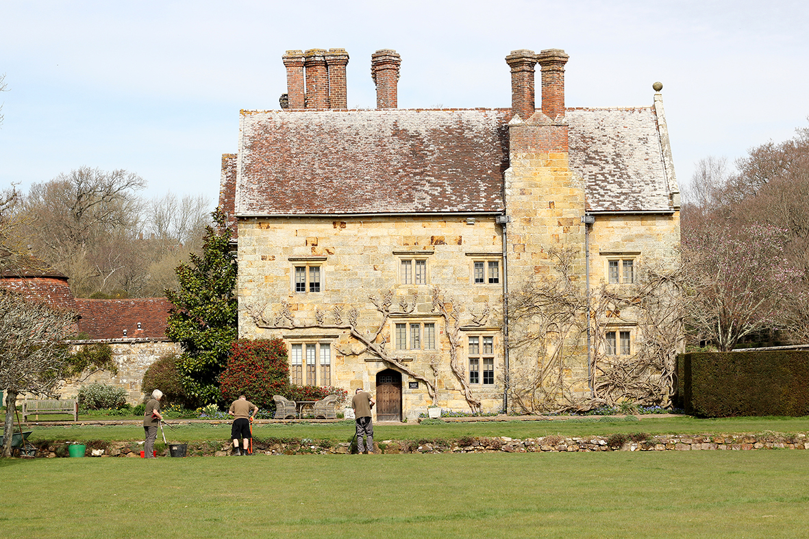 Gardeners at work behind the 17th century Jacobean house.