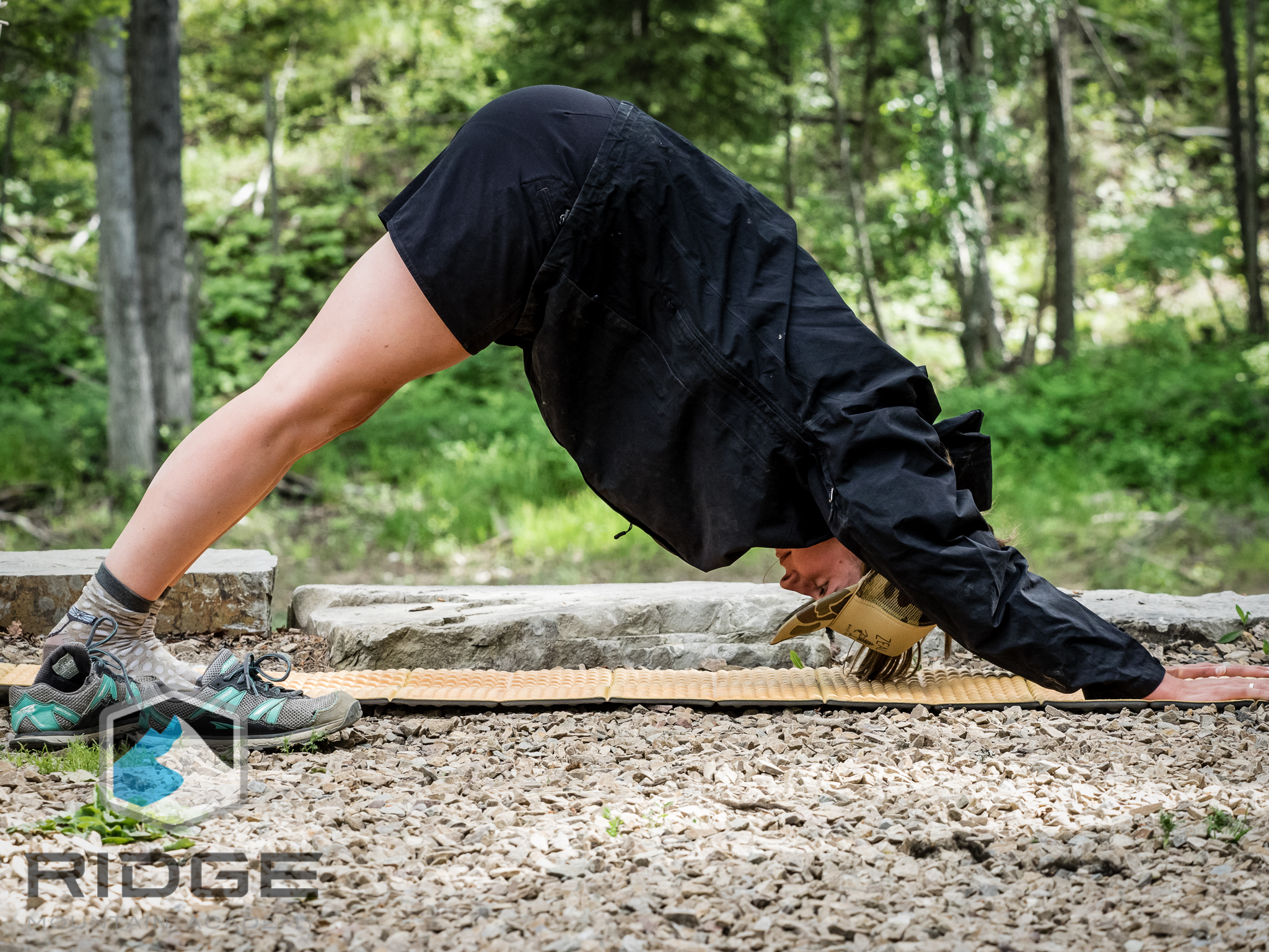 RIDGE Yoga coach, Cat, demonstrates Downward Dog in camp, before a day in the mountains.