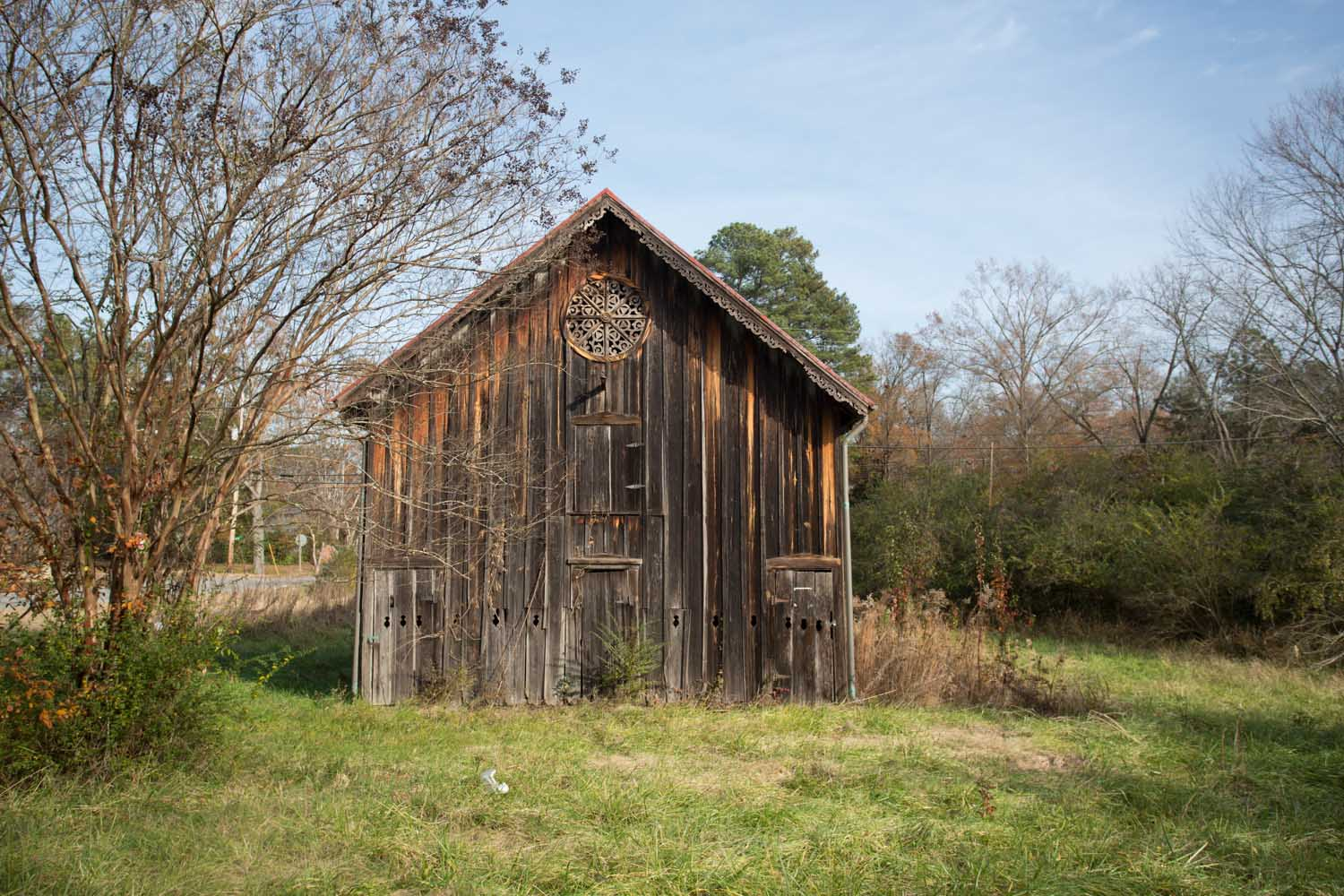 a favorite spot of mine, graves barn stand tall near downtown sparta, georgia. it has not changed much in the 15 years that i have been visiting, and its folk gothic woodwork gets me every time. this style is very unique to the area; to my knowledge there aren't any other structures with these forms. and, on this late fall day, the barn was the perfect backdrop for the colors of the drying grasses and dark plum-reds of the leaves nearby.