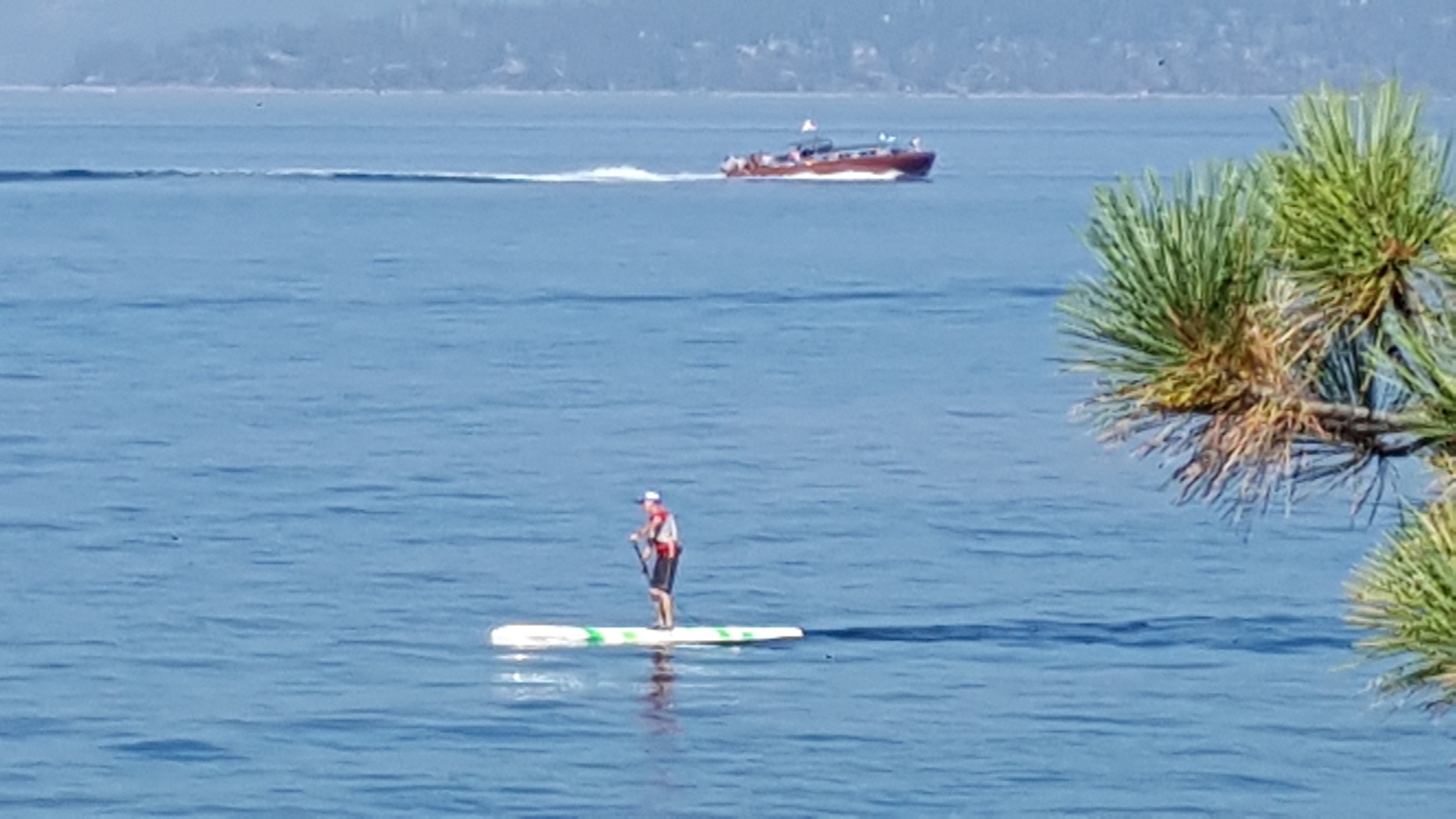"Tom paddles at Sand Harbor in Lake Tahoe with a yacht known as ""Thunderbird"" in the background."