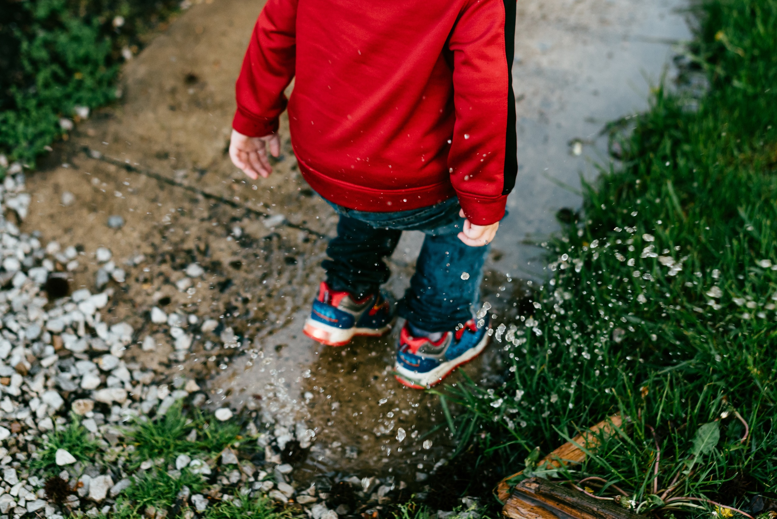 A child in a red coat splashes in a rain puddle on the sidewalk.