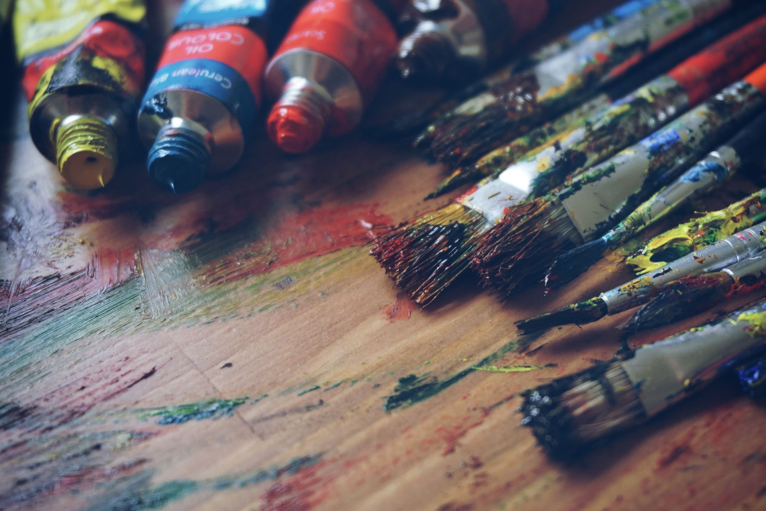 Open paint tubes in primary colors beside stained up paintbrushes on a wooden table.