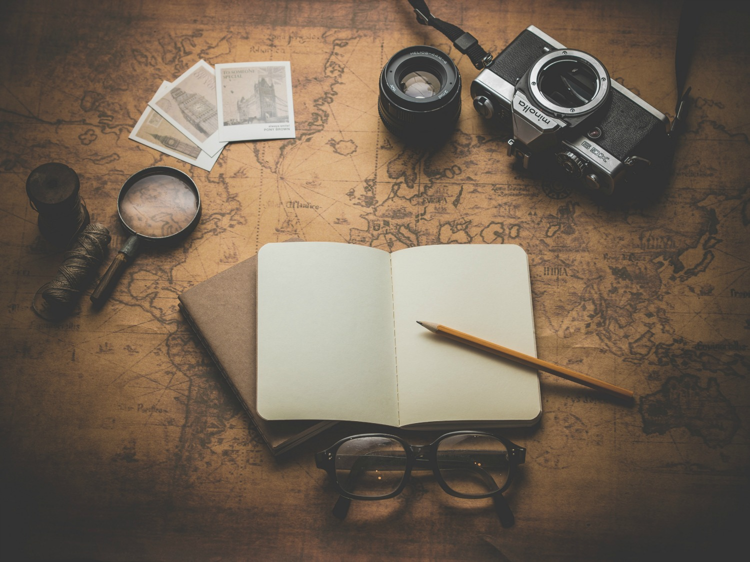 A map is spread out with vintage camera and other old looking travel paraphernalia. An open journal and pencil are the focus.