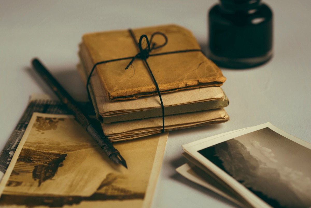 Stacks of bound letters and photos yellowed with age rest on a table along with a black fountain pen and matching inkwell.