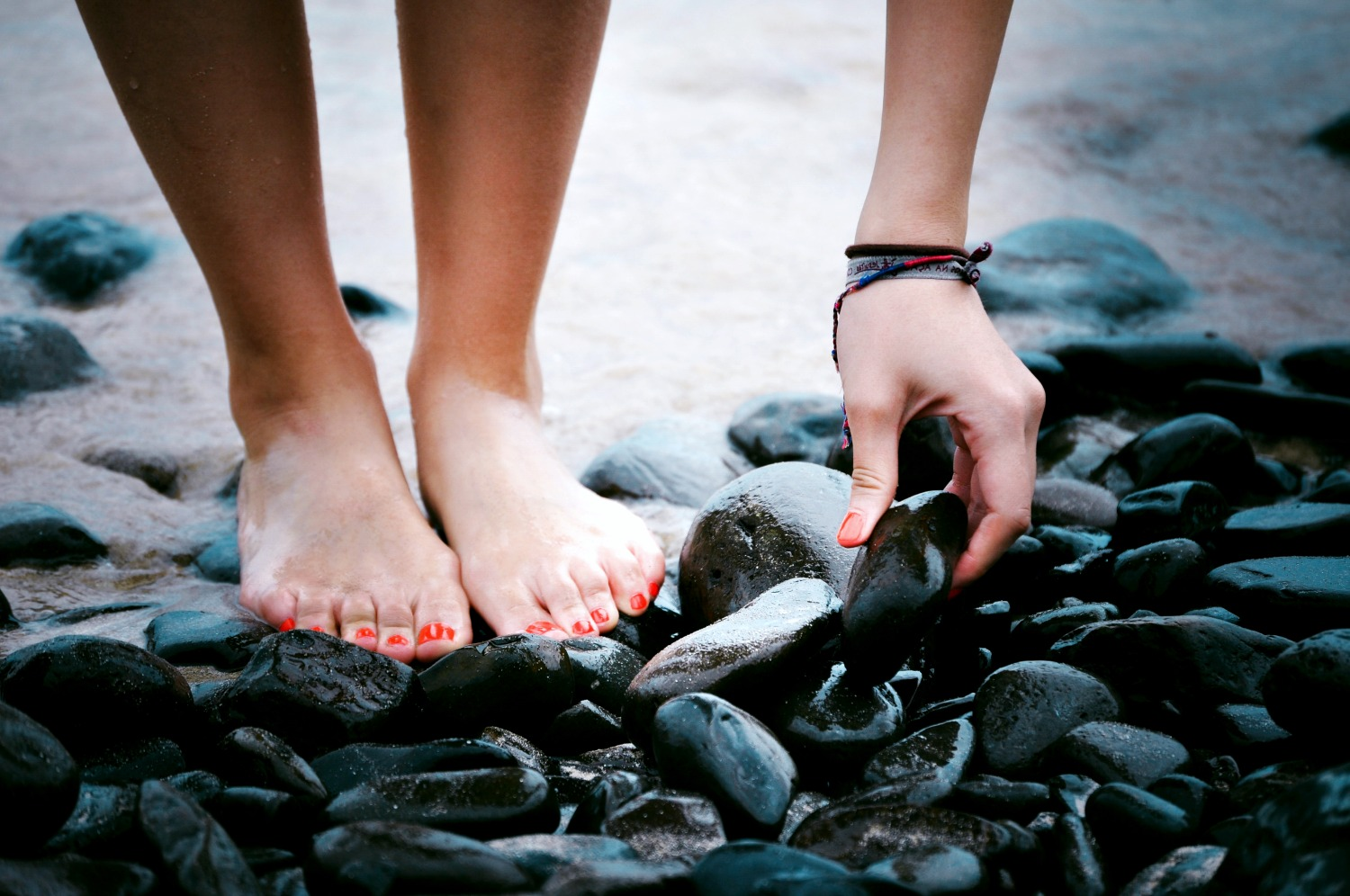 A person with bare feet and red painted nails reaches down to pick up a shiny black river stone.
