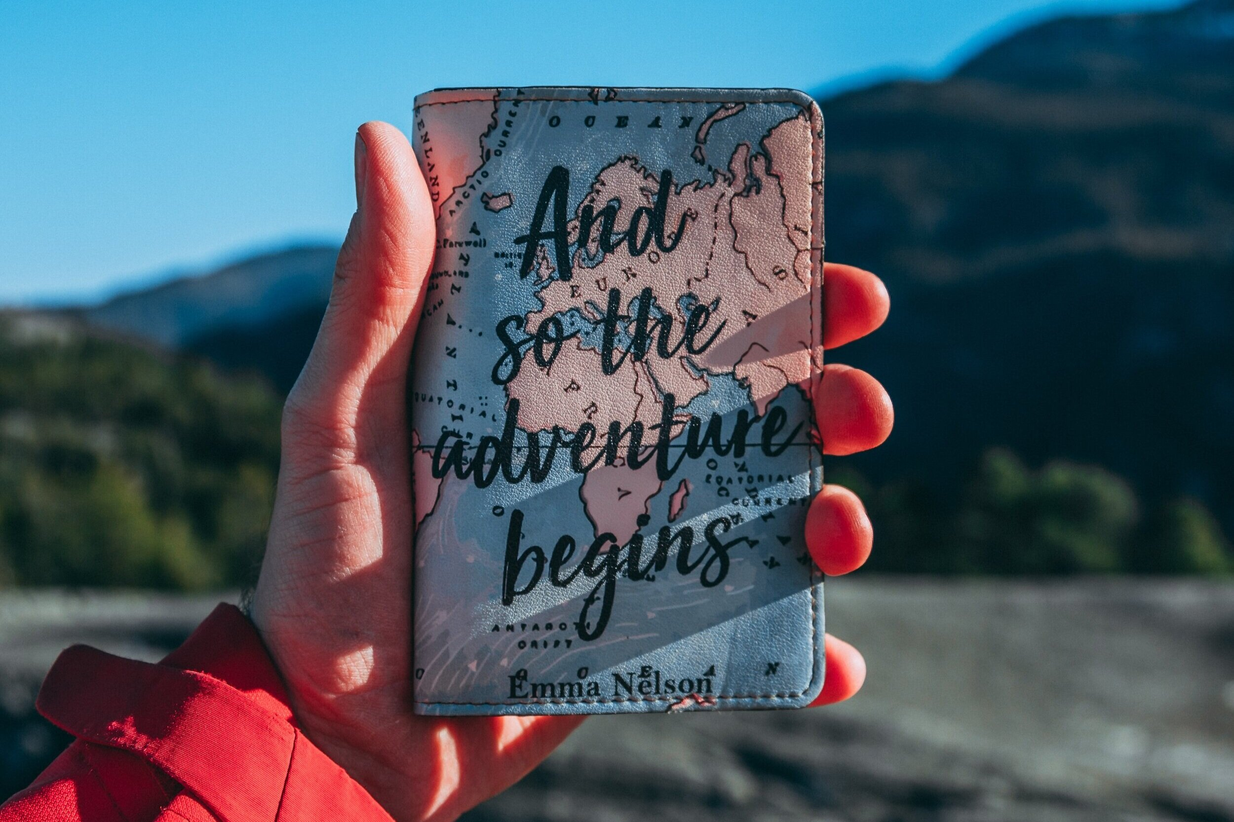 "A small travel journal is held aloft against a mountainous background, decorated with the words ""And so the adventure begins"" across a map."