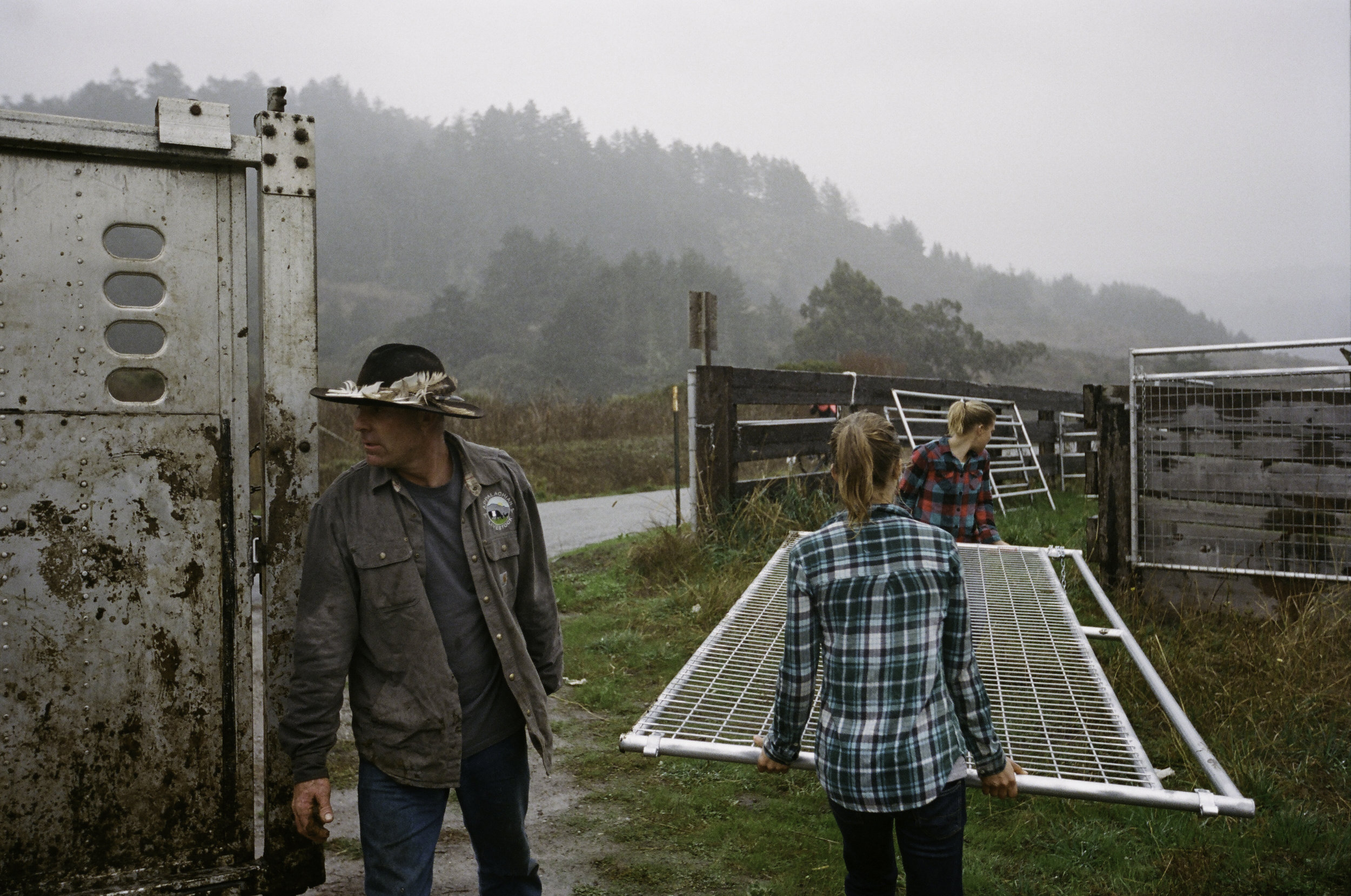 Erik, Johanna, and Ruth work to quickly unload fencing in the rain. - San Gregorio, CA