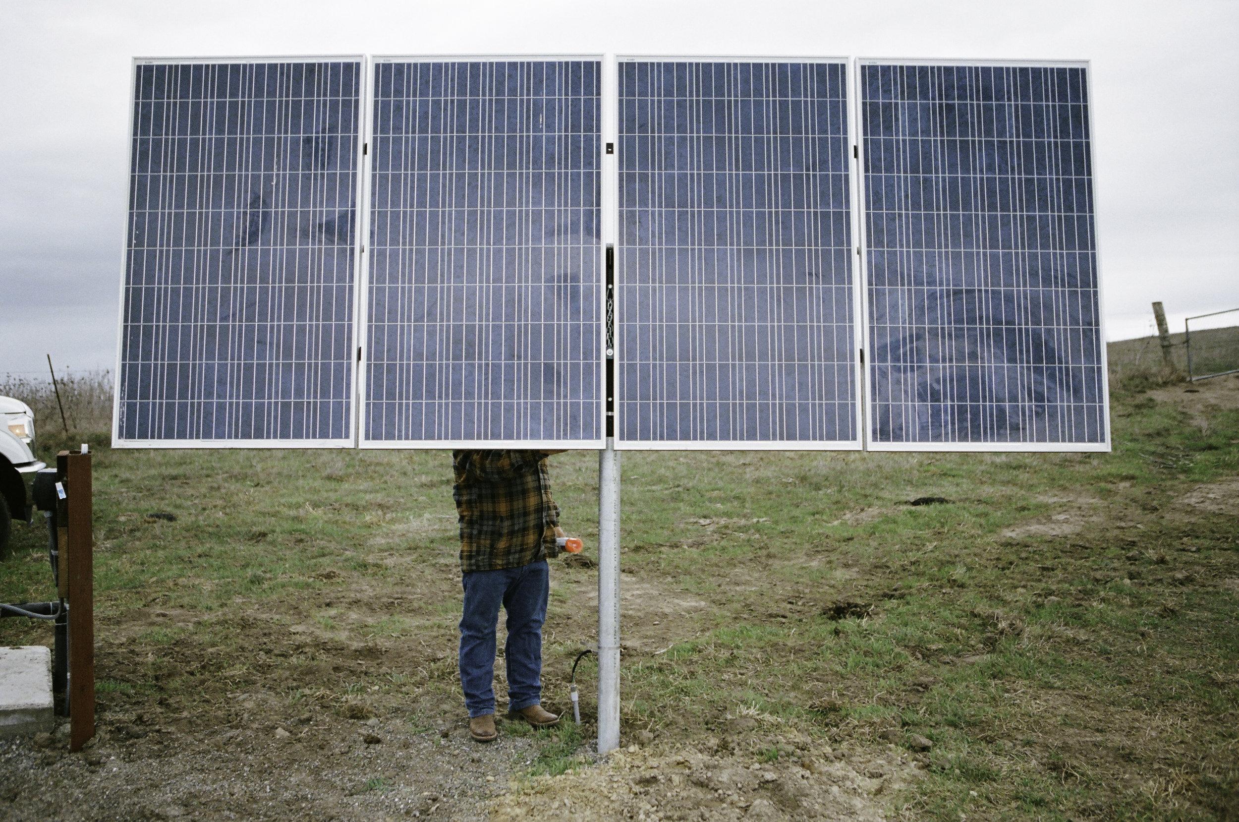 Loren reangling his newly installed solar panels that power his water pumps. - Petaluma, CA