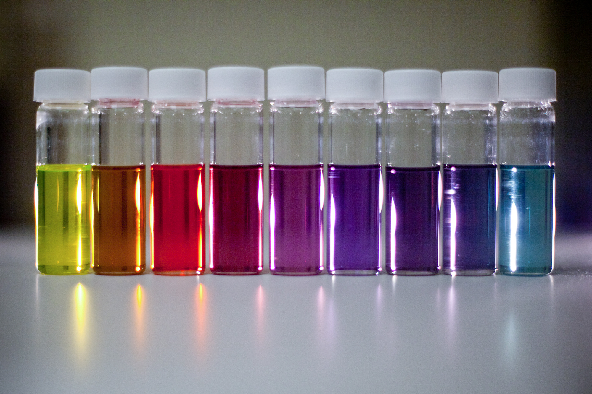 Materials Science and Engineering doctoral student Bong-Gi Kim prepares thin films of plastic for testing in solar cells. He works inside the nitrogen environment of the glove box so that the polymer material isn't contaminated by oxygen in the air. The vials display a rainbow of liquid polymers that absorb different parts of the solar spectrum.