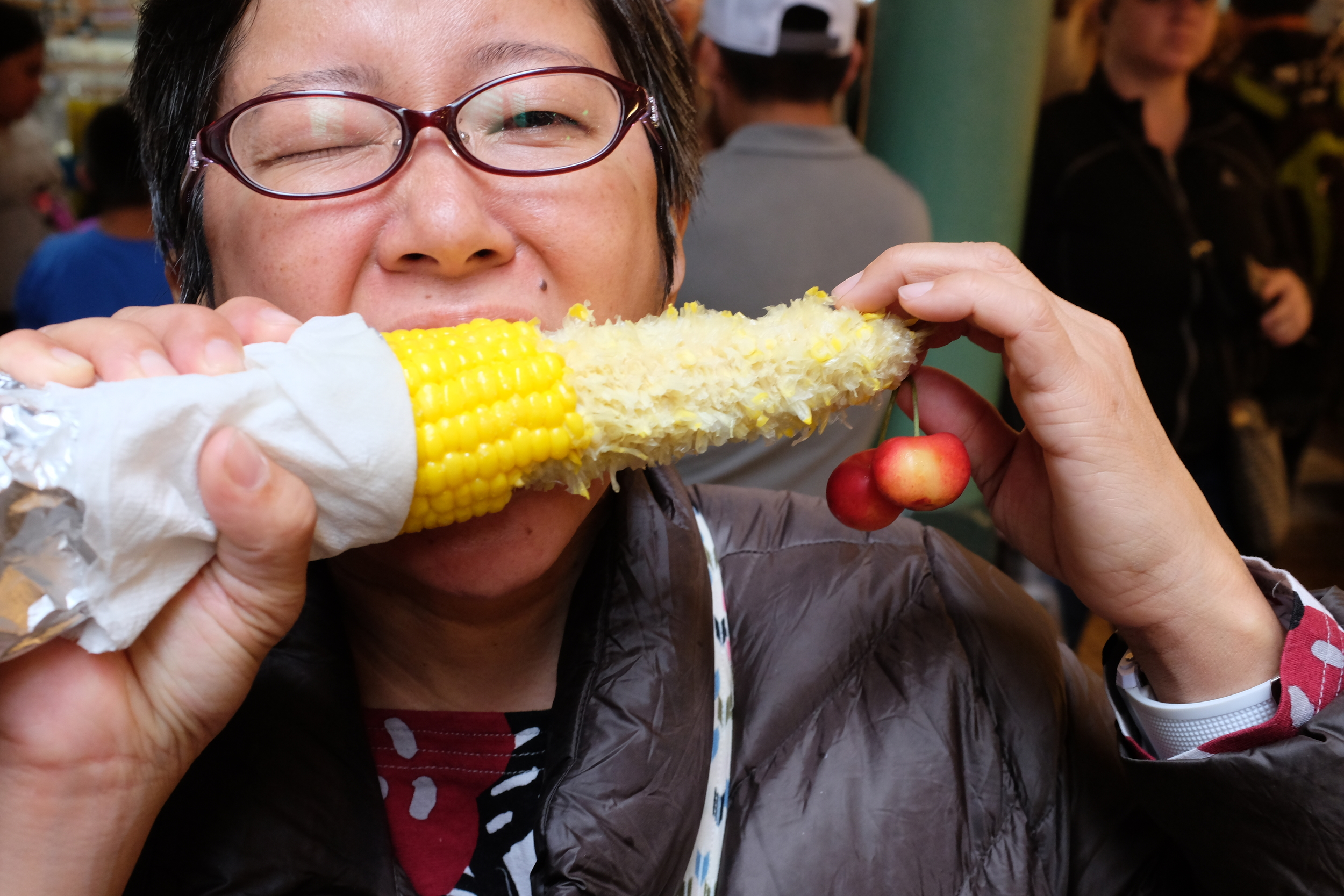 Eating roasted corn while holding Rainier cherries at the same time. (?)  Photo by Shishido.