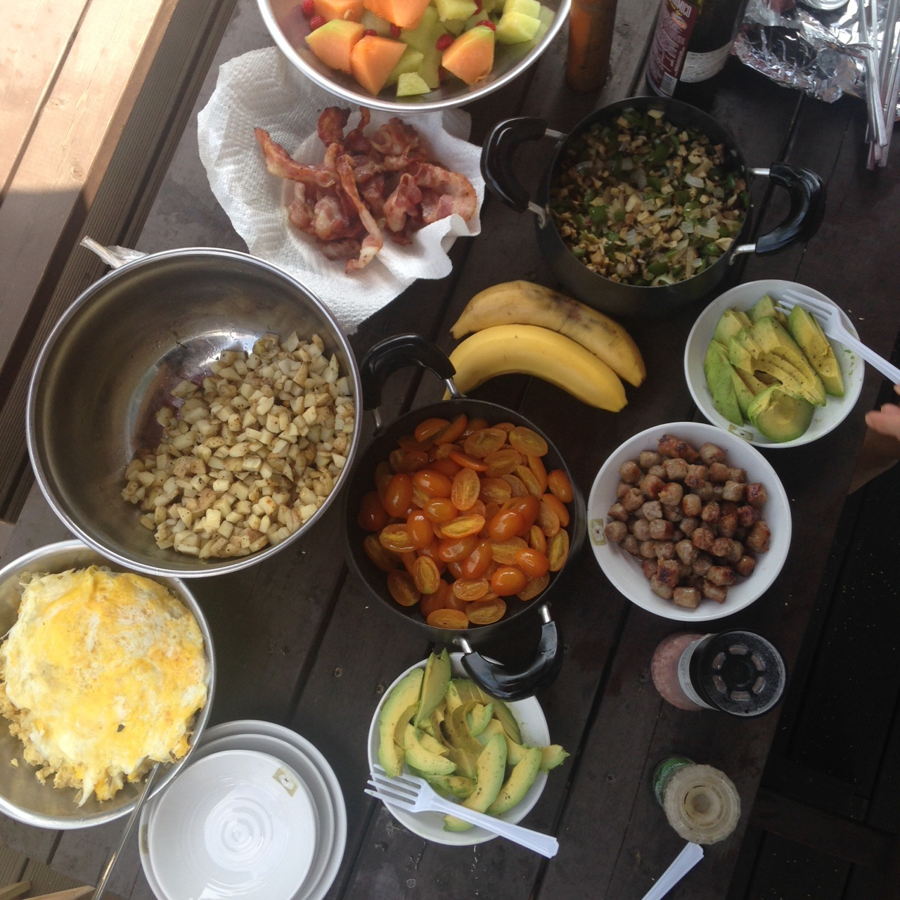 A Whole30-approved brunch feast on vacation: scrambled eggs, avocados, grilled tomatoes, sausages, grilled vegetable medley, home fries, fruit salad, bacon