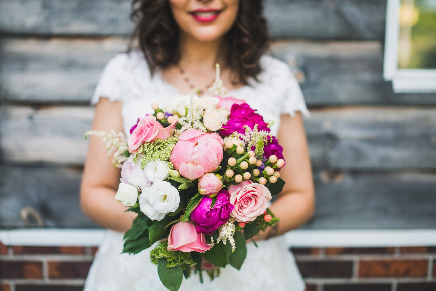 colorful bridal bouquet in shades of pink with wooden barn wall in the background during a country side wedding in quebec eastern twonships
