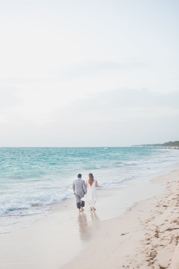 bride and groom walking holding hands on the beach on punta cana