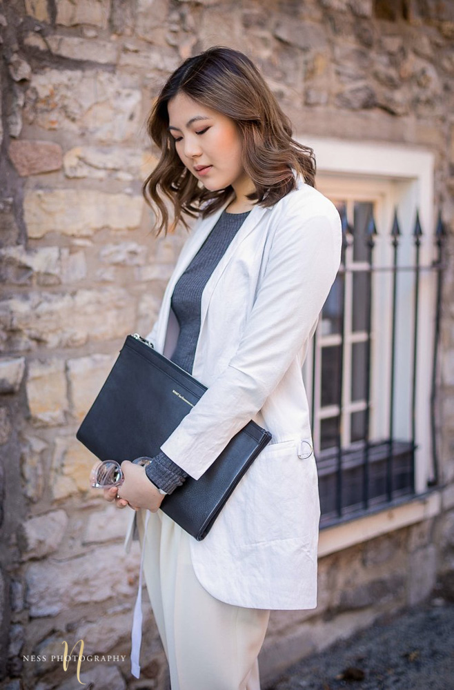 portrait of heydahye fashion blogger in white blazer in montreal old port with brick wall behind