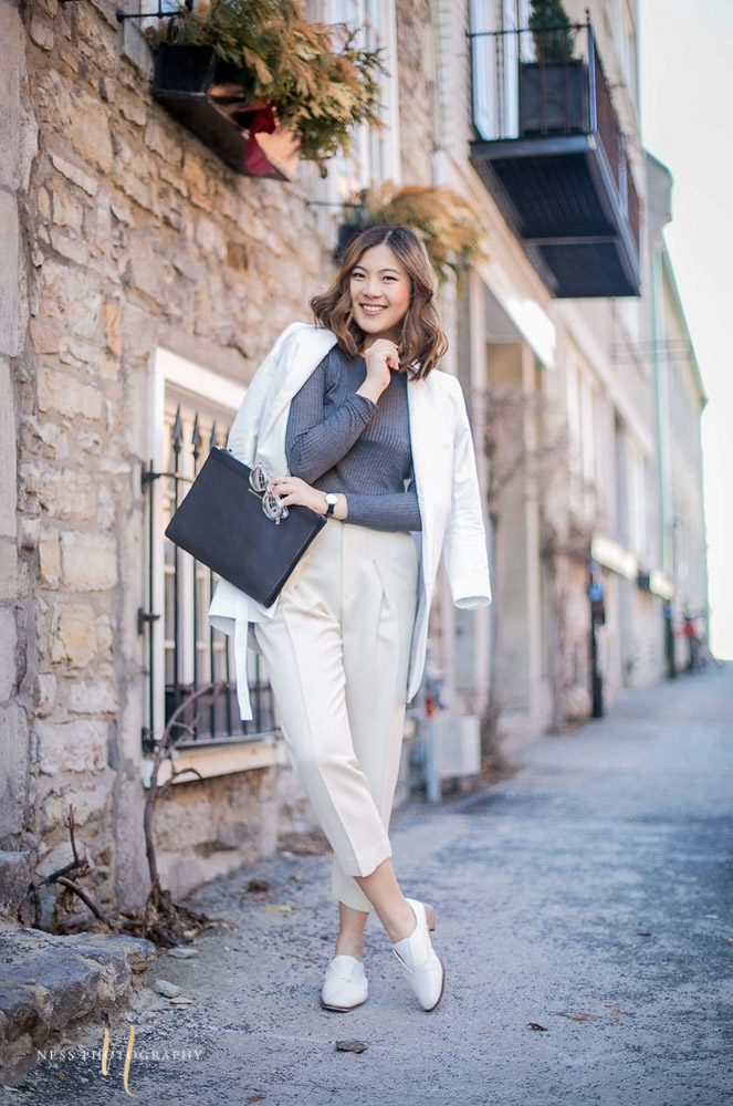 heydahye in white outfit and grey crop top in from of old montreal brick walls