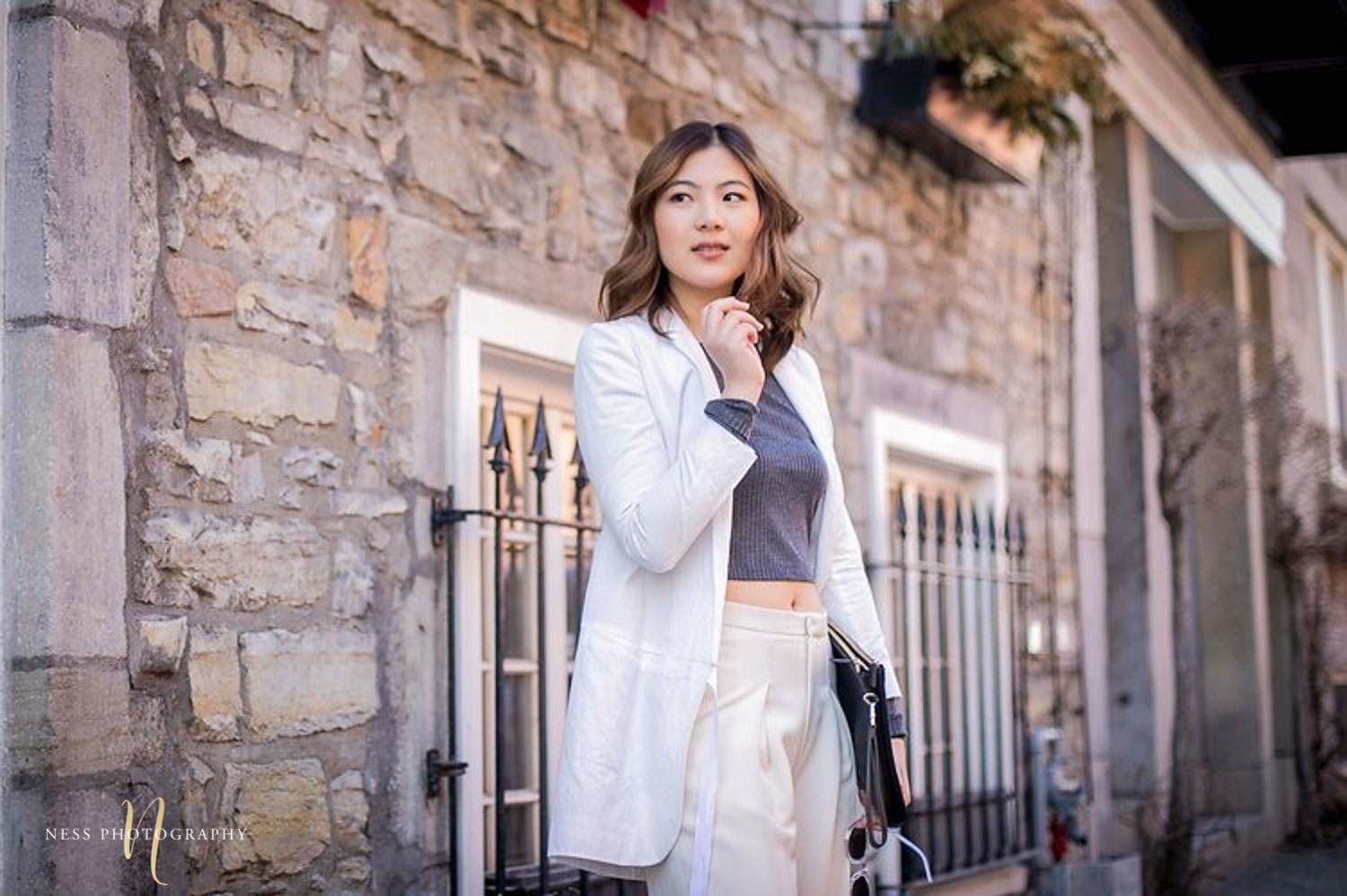 portrait in montreal vieux port of heydahye wearing white and holding sunglasses