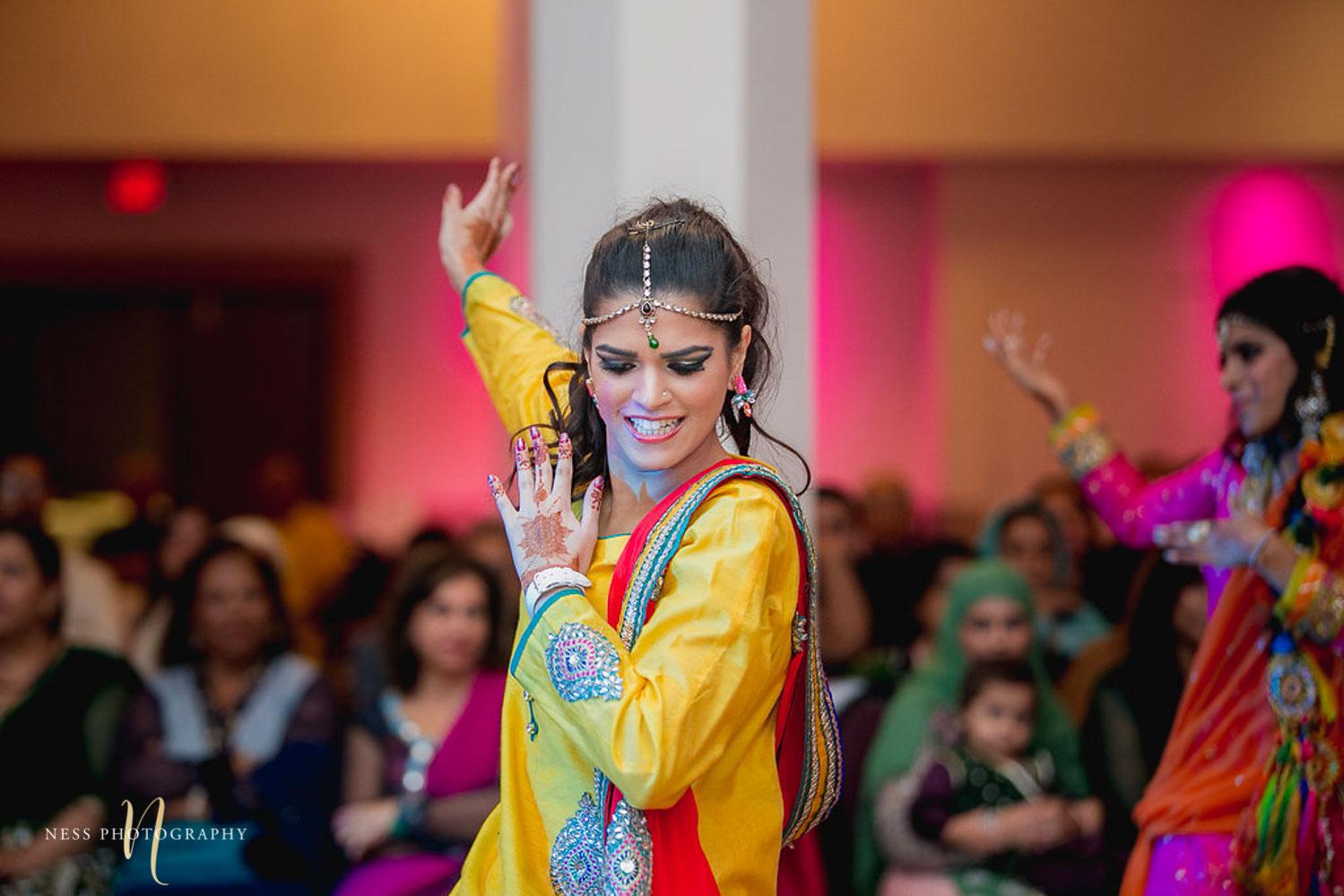 bridesmaid performing bollywood dance at mehendi wearing yellow shalwar kameez