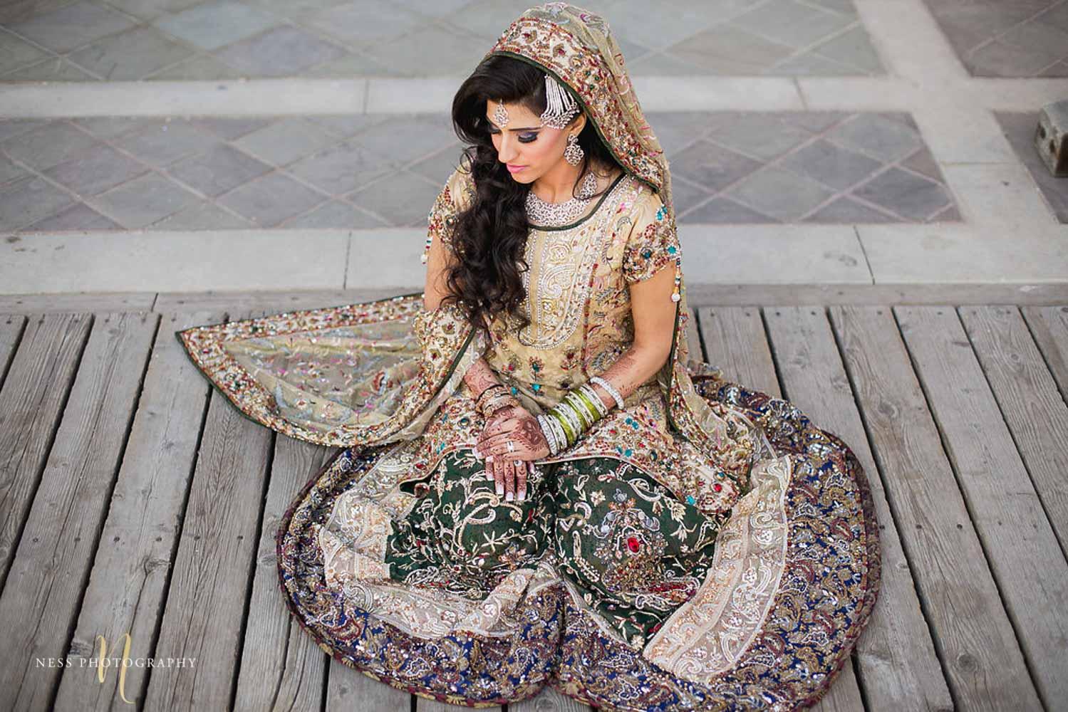 pakistani bride in green lehenga sitting with hands crosses at kariya park and looking down