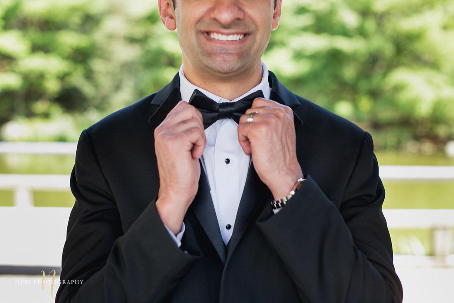 bridal photo of pakistani groom at kariya park fixing his bow tie