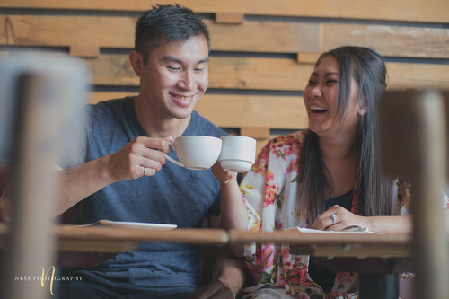 couple cheering with coffee cups during cacao70 engagement photoshoot