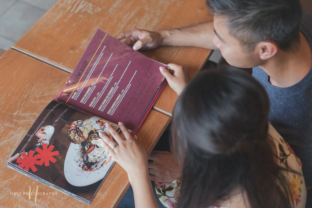 couple looking at cacao70 menu during montreal engagement photoshoot