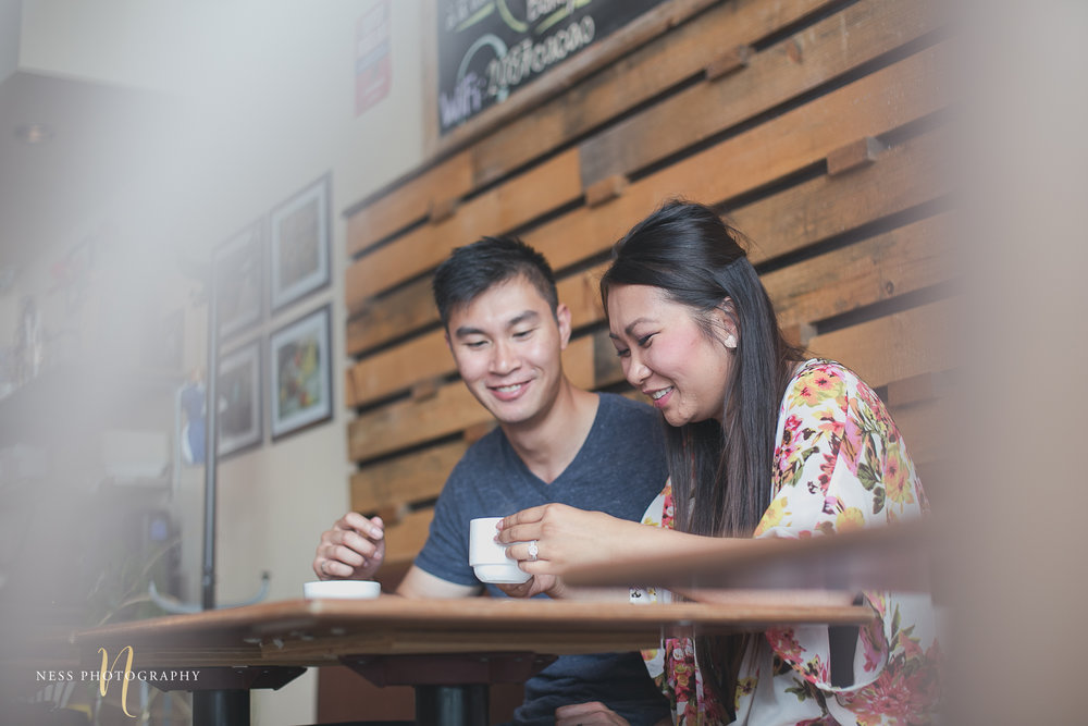 couple drinking coffee and maughing at cacao70 engagement photoshoot