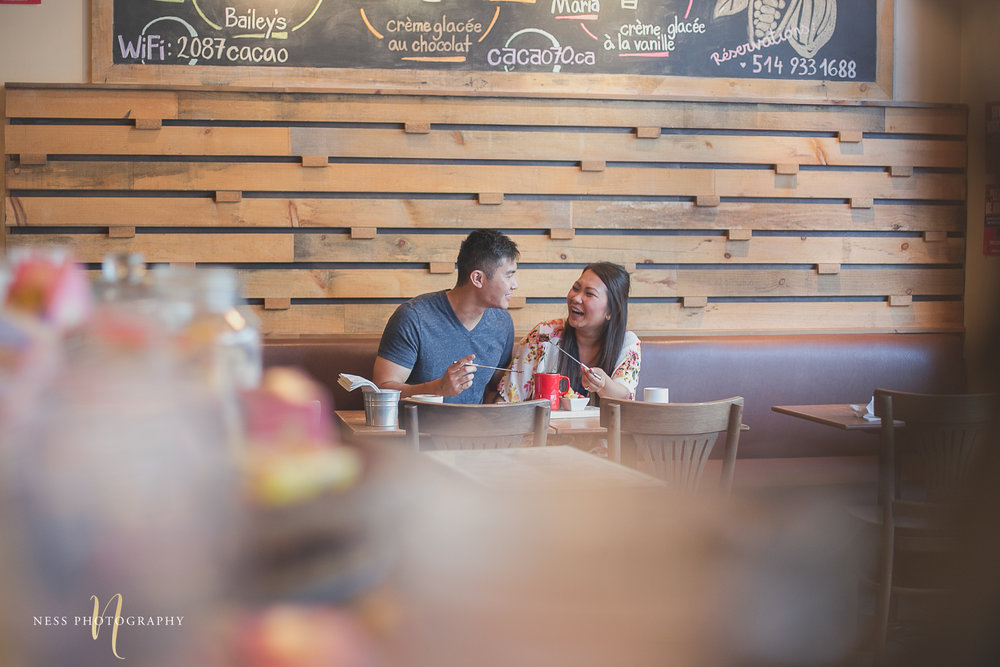 wide shot of couple eating chocolate fondu at caca70 montreal during their engagement photoshoot