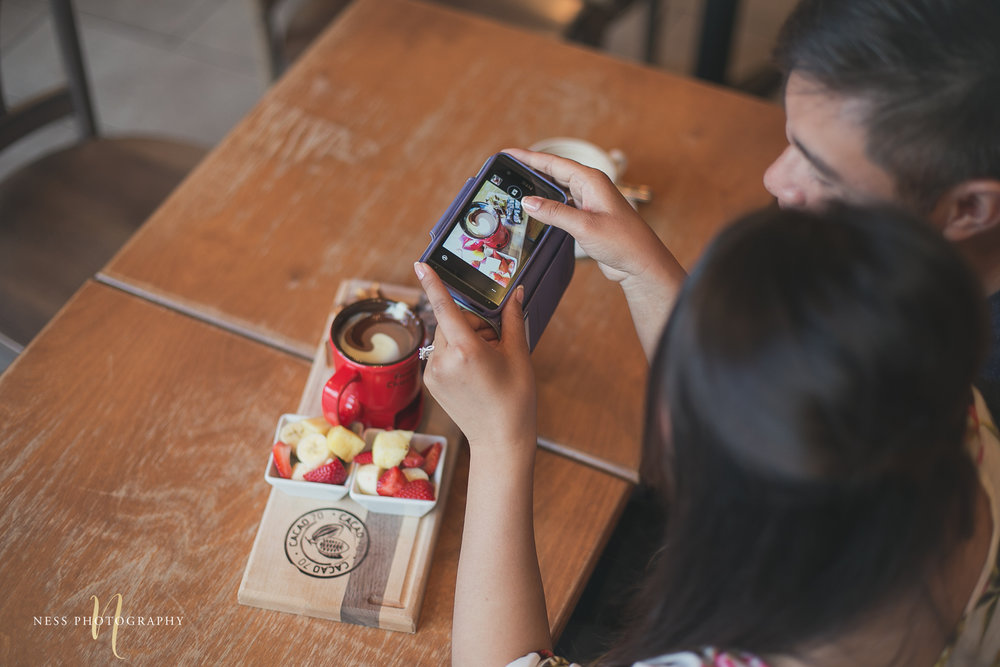 asian couple taking cellphone photos of their cacao70 chocolate fondue and fresh fruits
