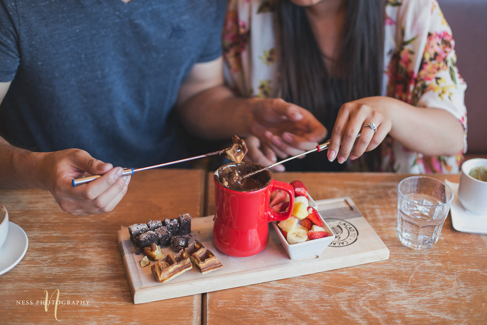 couple dipping their fresh fruits in cacao70 chocolate fondue during engagement photoshoot