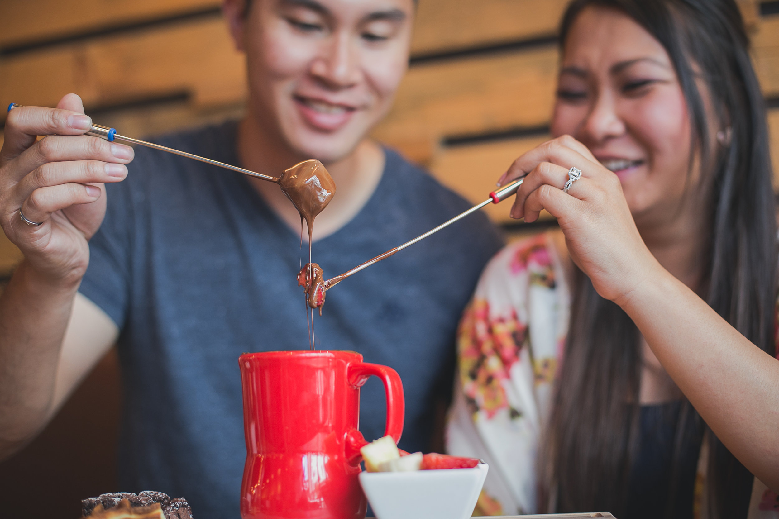 chocolate dripping off the fruits and couple blurry in the background during cacao70 engagement photoshoot