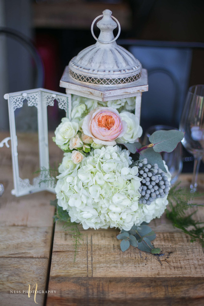 a close up of white flowers in rustic lantern at engagement Party in Montreal