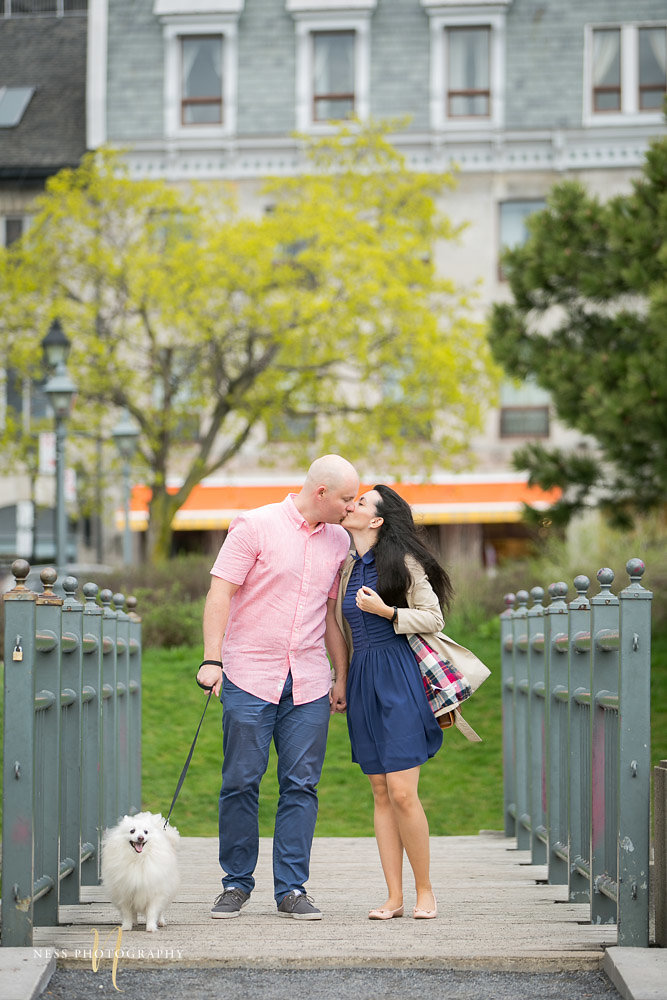 couple walking their dog and kissing on a bridge in the old port of montreal during their engagement photos
