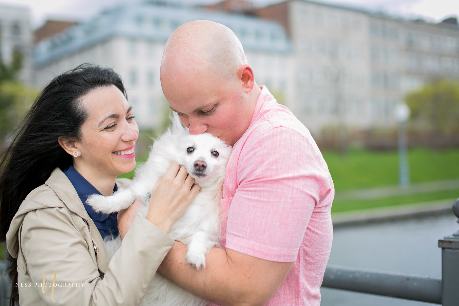 couple holding a dog and laughing during their engagement photoshoot in old port of montreal