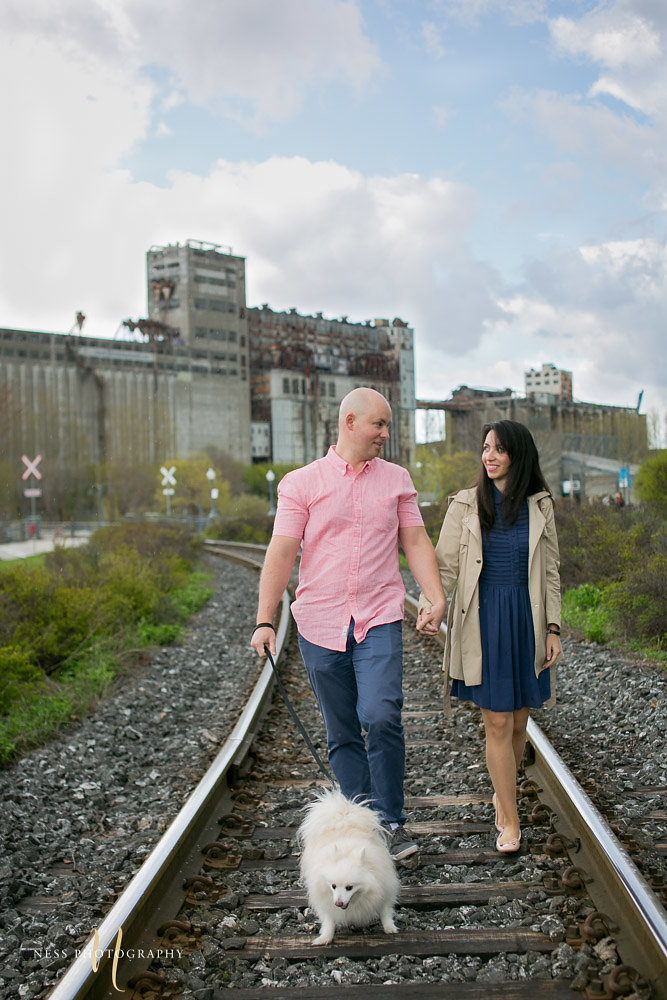 couple walking with their dog on train rails in old port of montreal during their engagement photoshoot