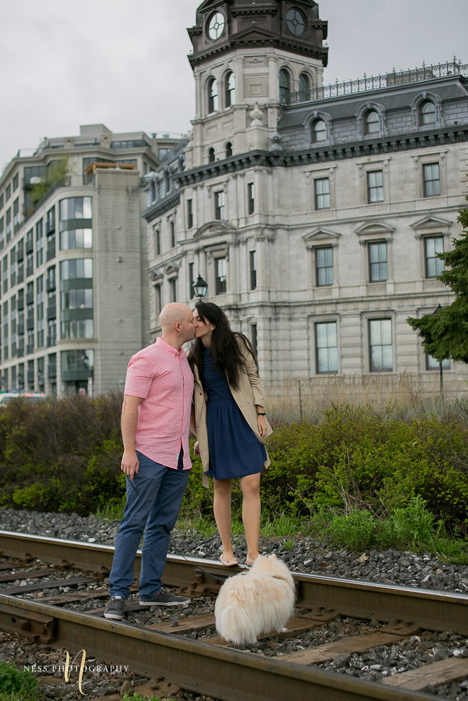 couple walking with their dog on train rails and kissing in old port of montreal during their engagement photoshoot