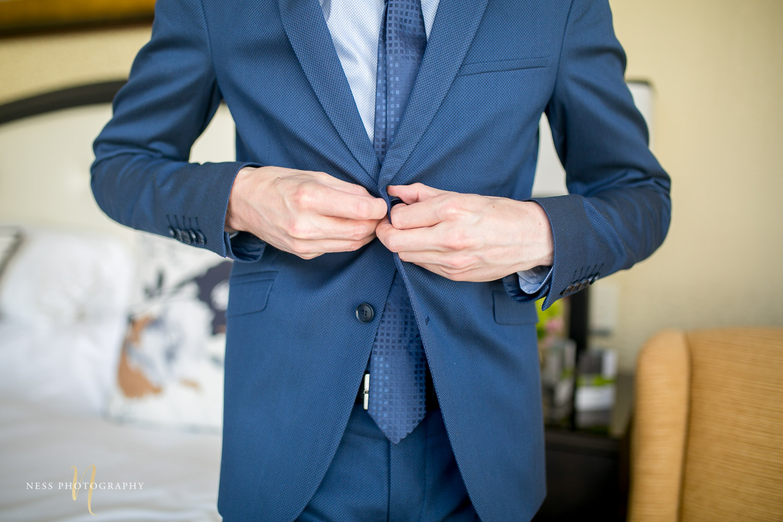 montreal elopement groom buttoning his jacket
