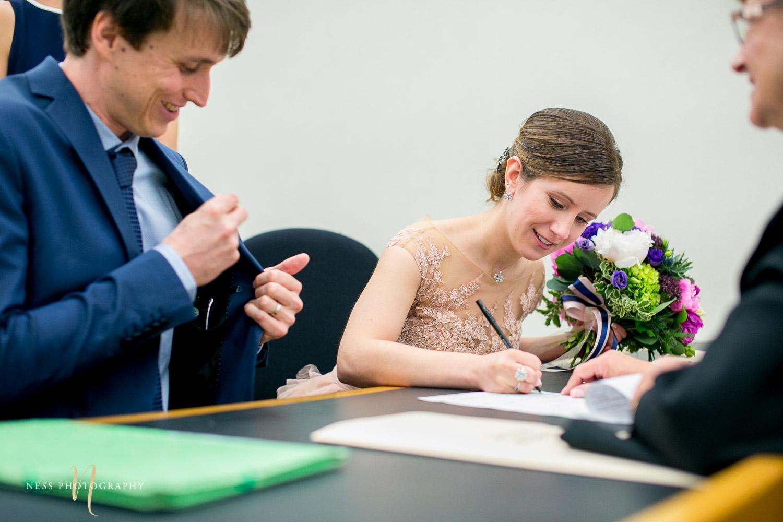 bride signs  during Montreal elopement at palais de justice