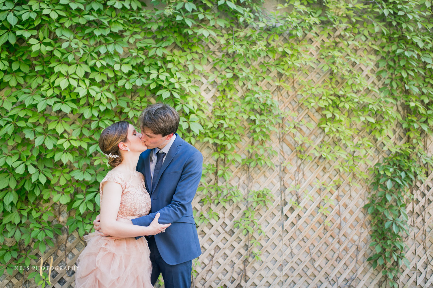 bride and groom kissing in front of vine wall during elopement wedding photos