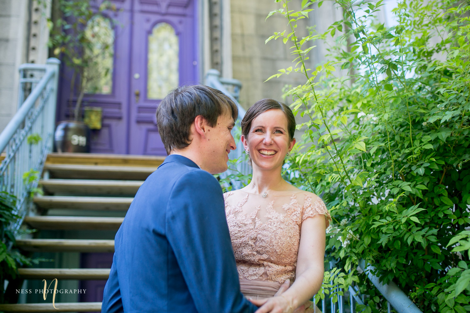 bride and groom laughing in front of purpule house in square saint louis