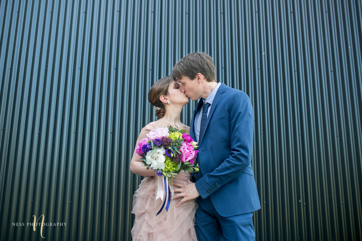 bride and groom kissing in front of shipping container in canal lachine for their montreal elopement