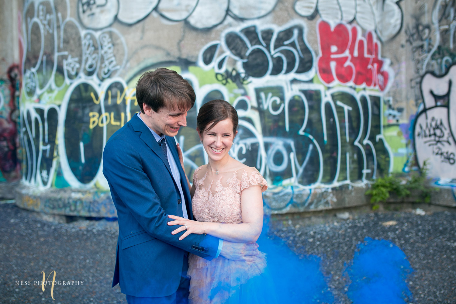 bride and groom in the middle of bleu smoke bomb in front of graffiti wall in canal lachine for their montreal elopement