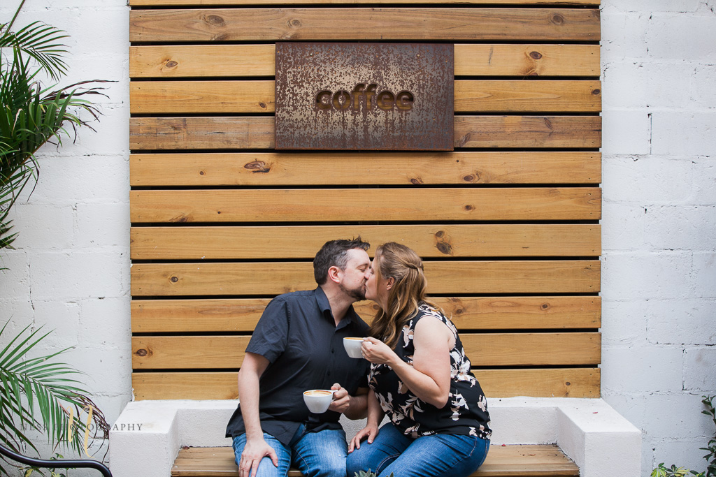 coupe kissing in front of coffee sign at Foundation coffee co engagement photoshoot- Tampa Florida  wedding photographer