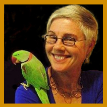 Photo of Rosemarie Garland-Thomson with a green parrot on her shoulder.