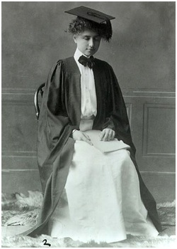 Photo of Helen Keller wearing a scholar's cap and gown and reading a document written in braille.