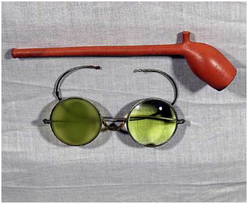 "The image of the famous painting ""Monet's Glasses"" which depicts a pair of green tinted glasses, folded and laid beneath a long clay pipe.  The images are against a grey background."