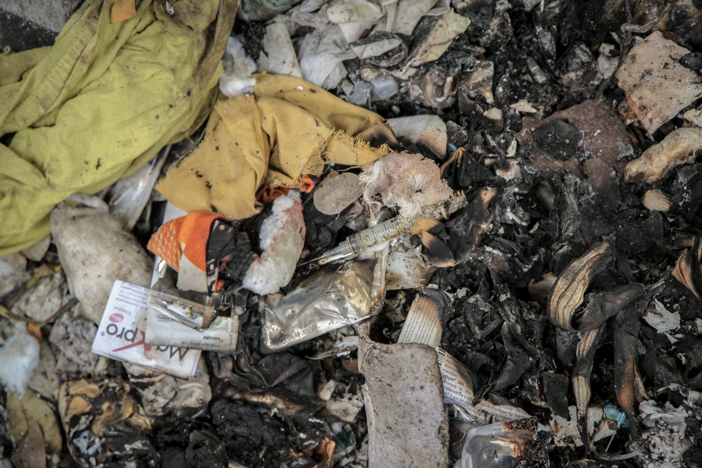 Unburnt hazardous waste with sharps and needles