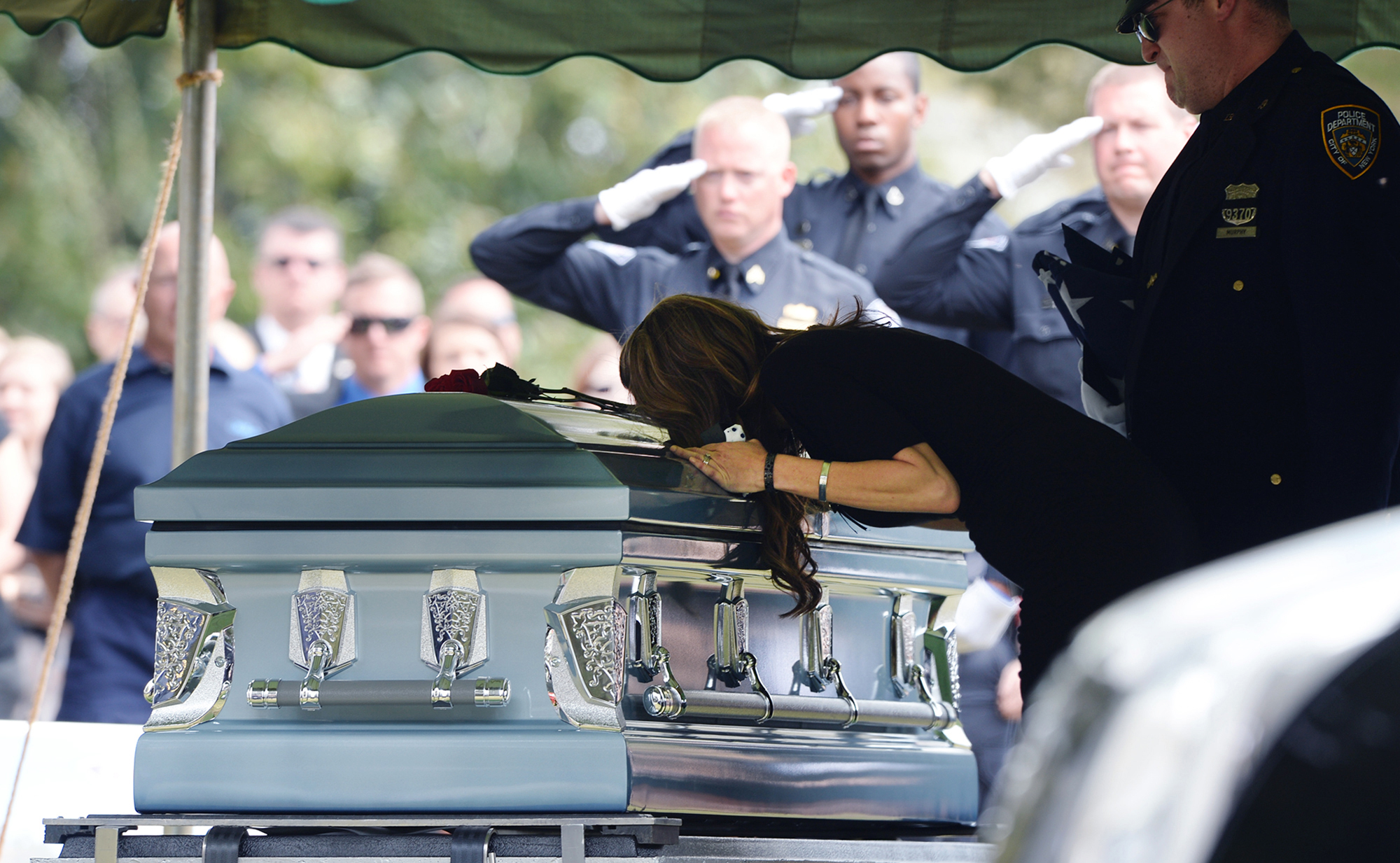 The wife of Greenville City Police Officer Allen Jacobs leans over his casket at the graveside service at Coleman Memorial Cemetery in Travelers Rest.