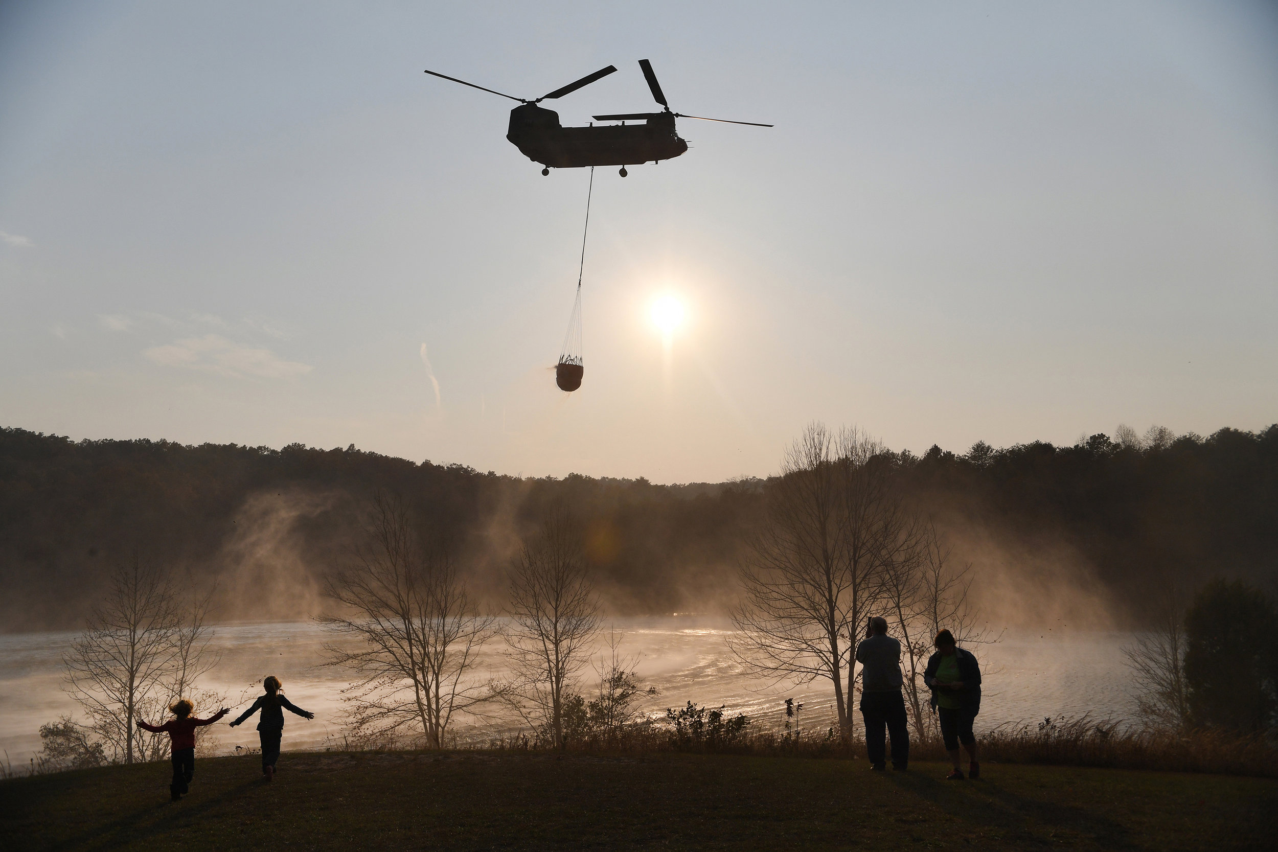 A Chinook pulls water out of Lake Oolenoy near Table Rock State Park on Tuesday, November 15, as firefighters continue to battle wildfires.