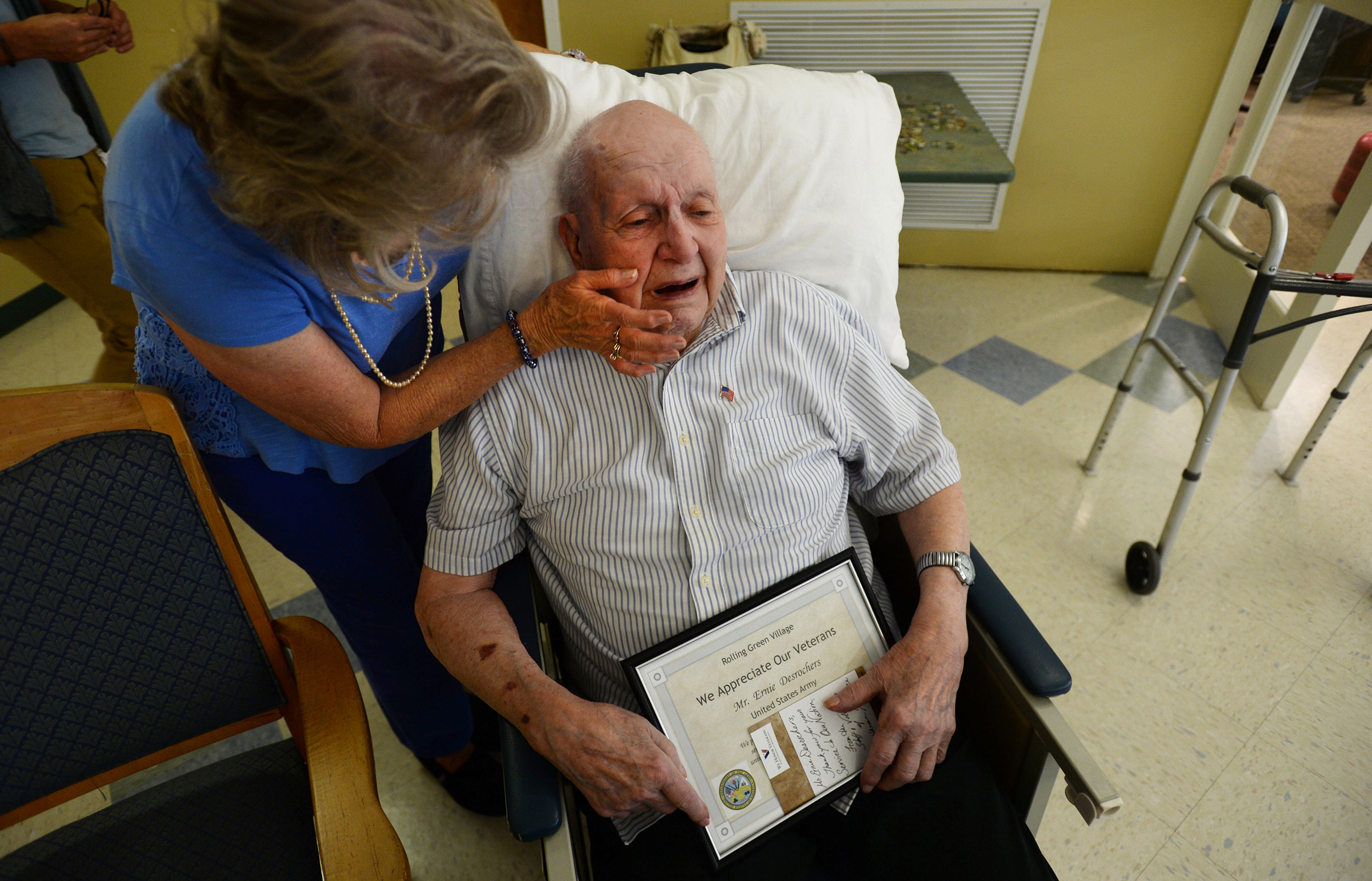 Carol Cole, left, congratulates her friend and Army veteran Ernie Desrochers after he received a certificate of appreciation and an American flag pin from Lutheran Hospice at Rolling Green Village on Tuesday.