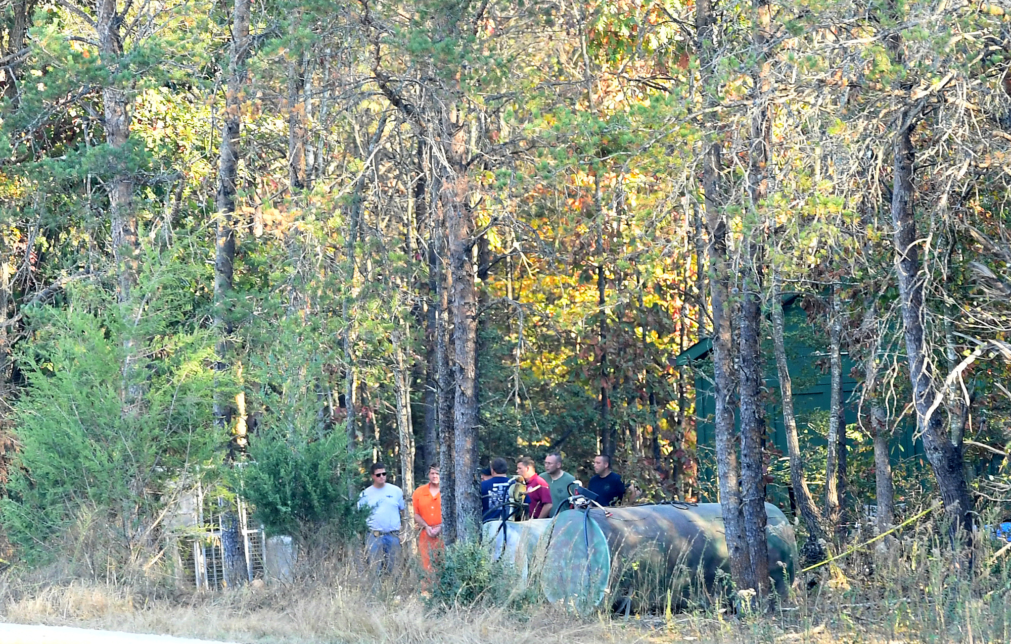 Todd Kohlhepp in handcuffs and an orange jumpsuit walks with deputies Saturday, November 5, 2016, on the property where a missing woman was found chained in a metal container in Woodruff.
